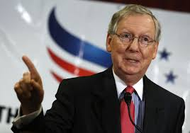 Mitch McConnell standing at a microphone during a rally gesticulating to make a point.